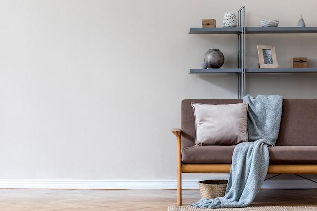 Nowoczesna aranżacja wnętrza salonu z brązową drewnianą sofą, szarym regałem, pledem, poduszką i eleganckimi dodatkami. koncepcja beżu i japandi. stylowy home staging. szablon. skopiuj miejsce.