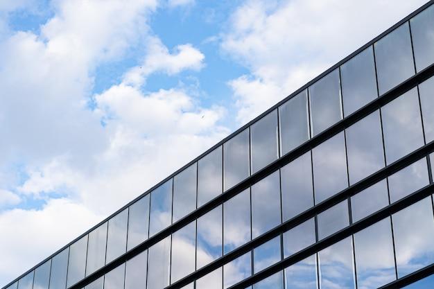 Nowoczesna architektura budynku ze szkła z niebieskim niebem i chmurami