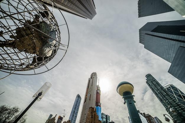 Nowoczesna architektura nowego jorku w usa w columbus circle z drapaczami chmur i słynnym globusem o zachodzie słońca.