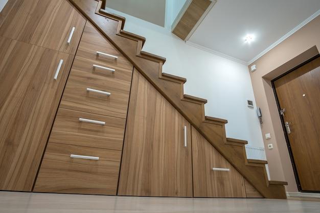 Nowoczesna architektura wnętrza z luksusowym korytarzem z błyszczącymi drewnianymi schodami w wielopiętrowym domu. niestandardowe szafki wysuwane na prowadnicach w szczelinach pod schodami. wykorzystanie przestrzeni do przechowywania.