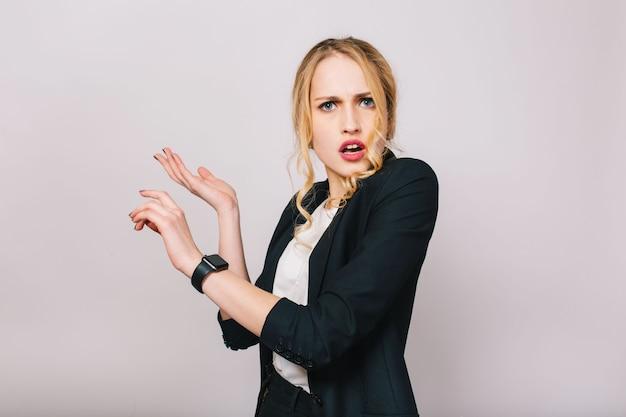 Nowoczesna atrakcyjna blond kobieta w białej koszuli i czarnej kurtce patrząc na białym tle. zdziwiona, pracownica, zajęta, bizneswoman, spotkanie