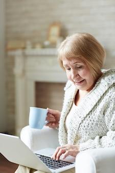 Nowoczesna babcia na czacie za pośrednictwem sieci społecznościowej