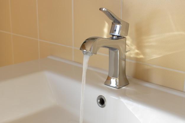 Nowoczesna bateria w żółtej łazience z bieżącą wodą, zbliżenie, widok z boku. higiena koncepcji, sprzątanie domu, oszczędność wody, problemy z zaopatrzeniem, zmniejszenie zużycia, świadoma konsumpcja. poziomy.