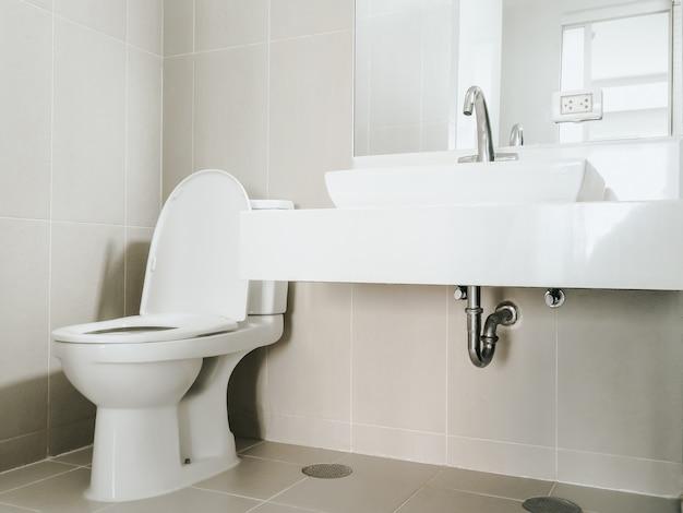 Nowoczesna bateria ze stali nierdzewnej na umywalce w łazience przy lustrze na ścianie i spłukiwana toaleta w rogu