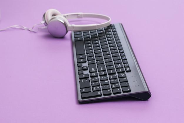 Nowoczesna bezprzewodowa klawiatura i białe słuchawki na fioletowym stole. urządzenia peryferyjne do komputera.