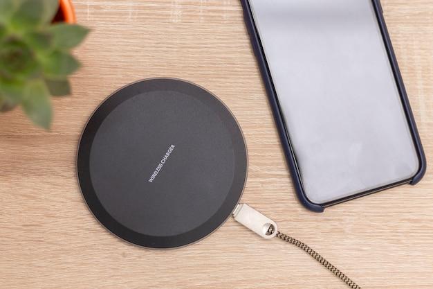 Nowoczesna bezprzewodowa ładowarka do urządzeń, telefonów i elektroniki. ładowarka do smartfona na stole, na górze napis wireless charger.