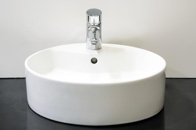Nowoczesna biała umywalka z kranem. wnętrze łazienki z umywalką i kranem.