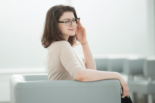 Nowoczesna biznesowa kobieta siedzi w recepcji biurowej. zdjęcie z miejscem na kopię