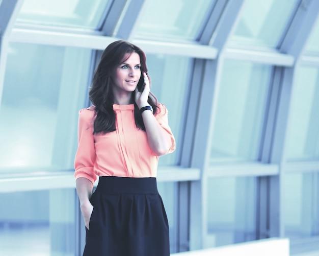 Nowoczesna biznesowa kobieta w biurze prowadząca dialog przez telefon z partnerami biznesowymi