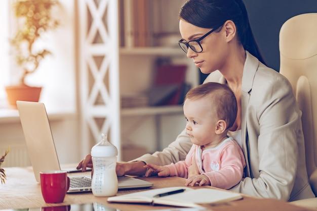 Nowoczesna bizneswoman poradzi sobie ze wszystkim. widok z boku młodej pięknej bizneswoman korzystającej z laptopa siedząc z córeczką na kolanach w jej miejscu pracy