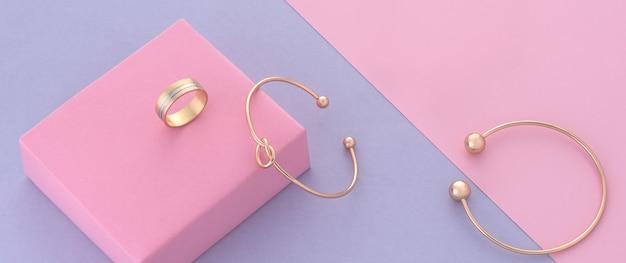 Nowoczesna bransoletka i pierścionek w kształcie węzła na różowym i fioletowym tle z kopią przestrzeni
