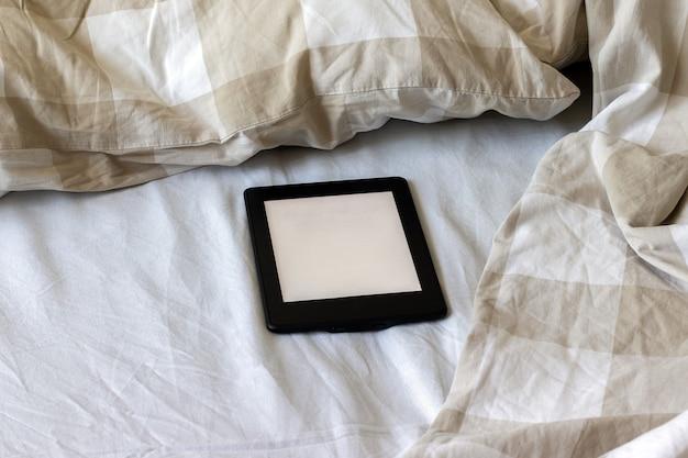Nowoczesna czarna książka elektroniczna z pustym ekranem na biało-beżowym tablecie makiety łóżka na pościeli