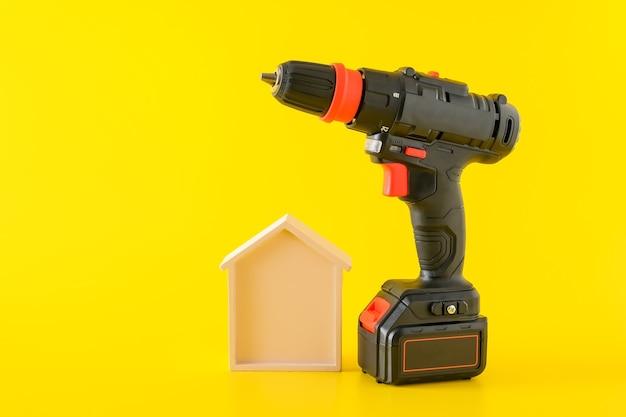 Nowoczesna czarna wkrętarka akumulatorowa, wiertarka z akumulatorem i drewniany dom, miejsce na tekst, koncepcja budowy lub renowacji