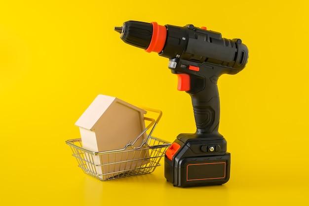 Nowoczesna czarna wkrętarka akumulatorowa, wiertarka z akumulatorem i drewniany domek w koszyku, miejsce na tekst, koncepcja budowy lub renowacji