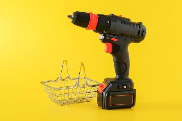 Nowoczesna czarna wkrętarka akumulatorowa, wiertarka z pustym koszem na zakupy, miejsce na tekst