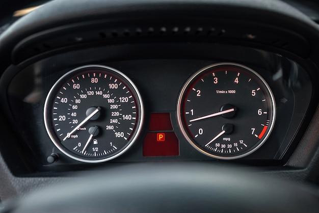 Nowoczesna deska rozdzielcza samochodu. ścieśniać. prędkościomierz z podwójnym wskaźnikiem i obrotomierz z białymi strzałkami.