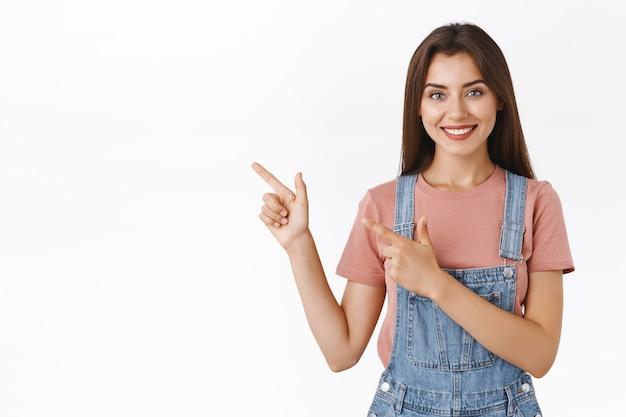 Nowoczesna, dobrze wyglądająca, pewna siebie, asertywna kobieta wskazująca lewy górny róg i uśmiechający się aparat, polecająca skorzystanie z kuponu promocyjnego lub proponująca dobry wybór na wakacje, stoisko na białym tle