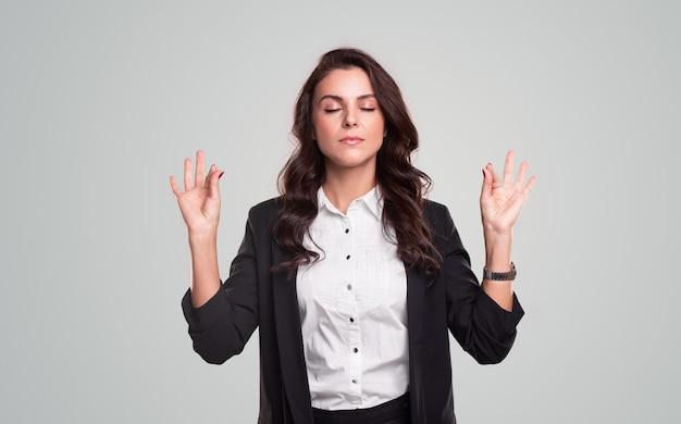 Nowoczesna dorosła biznesowa dama w eleganckich ubraniach z zamkniętymi oczami i gestem mudry medytującym dla złagodzenia stresu na szarym tle