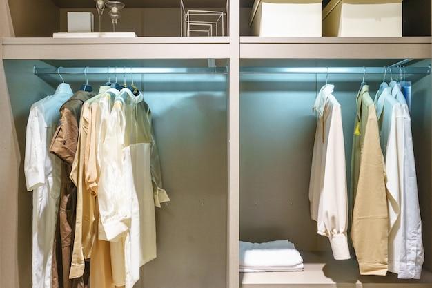 Nowoczesna drewniana szafa z ubraniami wiszącymi na szynie w spacerze w szafie projektowania wnętrz