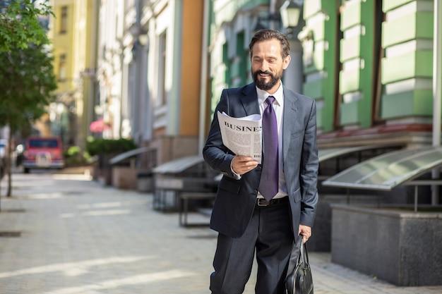 Nowoczesna dzielnica. przyjemny biznesmen czyta gazetę idąc do pracy
