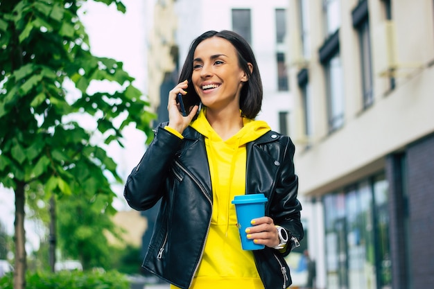 Nowoczesna dziewczyna! młoda, nowoczesna dziewczyna, ciesząca się dniem, ze swoim smartfonem, wygodnym kubkiem termicznym i nowym, ładnym smartwatchem.