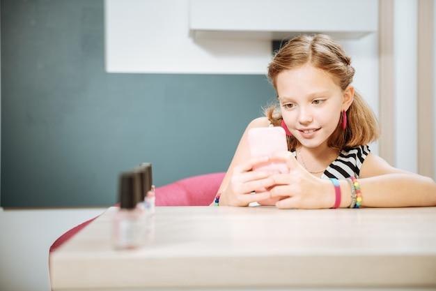 Nowoczesna dziewczyna. nowoczesna nastolatka robi zdjęcie kolorów lakieru do paznokci czeka na swoją mamę w salonie piękności