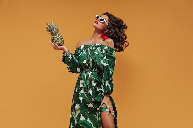 Nowoczesna dziewczyna z kręconymi włosami z czerwonymi, jaskrawymi dużymi ustami i niezwykłymi kolczykami w stylowej zielono-białej sukience i okularach przeciwsłonecznych