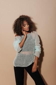 Nowoczesna dziewczyna z krótkimi włosami brunetki w białym swetrze i czarnych stylowych spodniach pozuje z zamkniętymi oczami na beżowej ścianie...