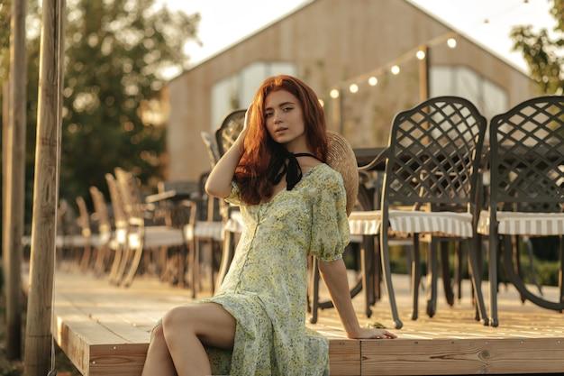 Nowoczesna dziewczyna z piegami, czarnym bandażem na szyi i imbirową fryzurą w letniej stylowej sukience patrząc z przodu na tarasie kawiarni