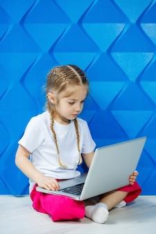Nowoczesna dziewczynka używa laptopa leżącego na podłodze z nogami patrząc w kamerę. śmieszne dziecko na jasnym niebieskim tle ściany. nowoczesna bezprzewodowa technologia internetowa