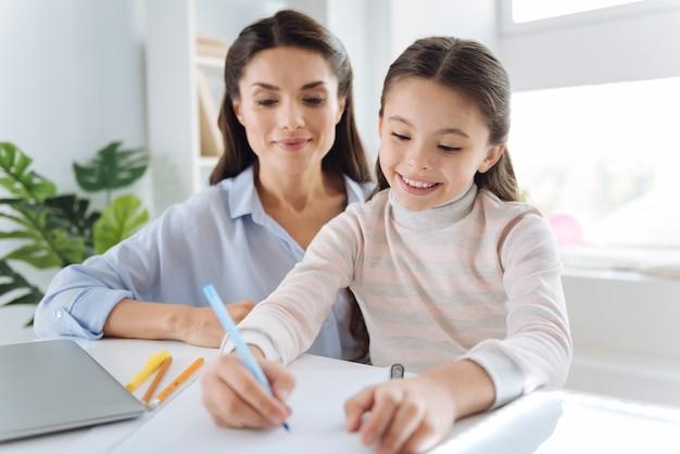 Nowoczesna edukacja. ładny miły inteligentny dziewczyna trzyma pióro i robienie notatek siedząc razem z matką