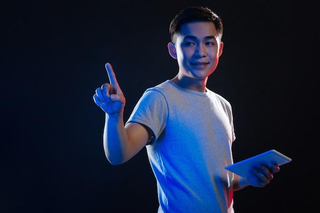 Nowoczesna elektronika. pozytywny młody człowiek za pomocą tabletu, naciskając przezroczysty ekran
