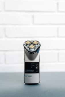 Nowoczesna elektryczna maszynka do golenia umieszczona na szarym stole na białym murem w domu