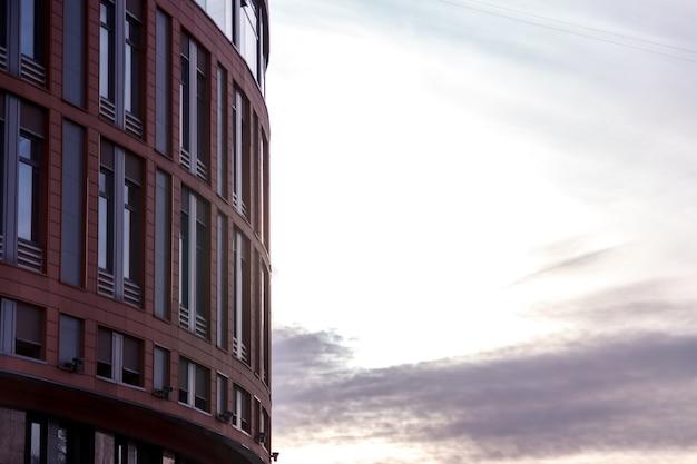 Nowoczesna elewacja biurowca to fragment abstrakcyjny, z błyszczącymi oknami w konstrukcji stalowej.