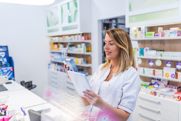 Nowoczesna farmaceuta z cyfrowym tabletem szukającym produktów w bazie danych.