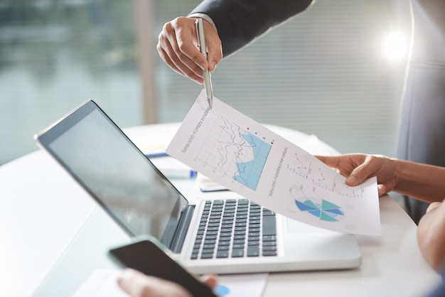 Nowoczesna firma teem coworking za pomocą wykresów i laptopa w biurze