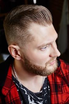 Nowoczesna fryzura dla mężczyzn hipster, idealna fryzura dla mężczyzn z długimi włosami. retro fryzura w salonie fryzjerskim