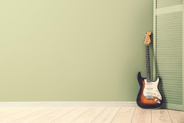 Nowoczesna gitara basowa i składany ekran w pobliżu kolorowej ściany