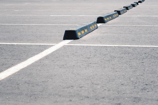 Nowoczesna gumowa bariera dla samochodów na letnim parkingu.