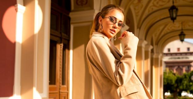 Nowoczesna i ładna dziewczyna w beżowym płaszczu stojąca w pobliżu budynku na zewnątrz. efektowne okulary przeciwsłoneczne na twarzy, makijaż i stylowa fryzura na ogonie, ręka przy twarzy, dużo letniego światła, ostatnie ciepłe dni