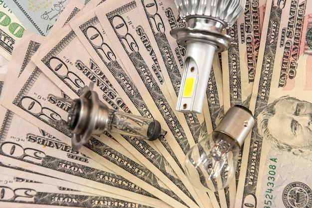 Nowoczesna jasna żarówka samochodowa na tle dolara, koncepcja sprzedaży sale