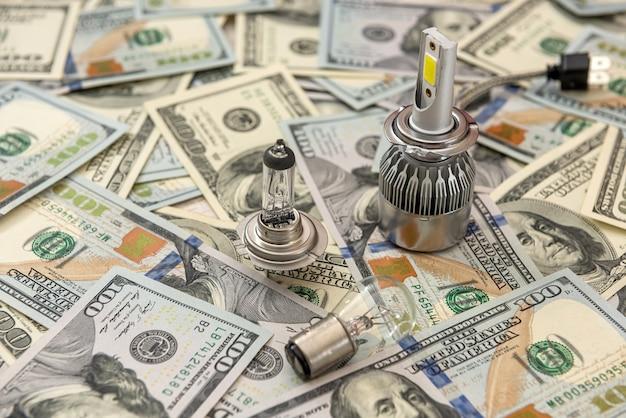 Nowoczesna jasna żarówka samochodowa na tle dolara, koncepcja sprzedaży