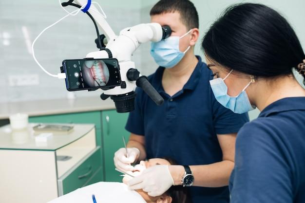 Nowoczesna klinika stomatologiczna z narzędziem mikroskopowym do leczenia pacjentów. ręka lekarza w rękawicy ochronnej stawiając mikroskop medyczny. mężczyzna dentysta używa mikroskopu. sprzęt medyczny, przychodnia stomatologiczna