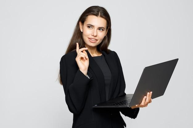 Nowoczesna kobieta biznesu w klasycznym garniturze korzystająca z laptopa