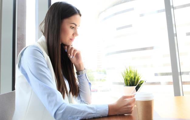 Nowoczesna kobieta pije kawę w kawiarni biurowej w porze lunchu i korzysta z tabletu