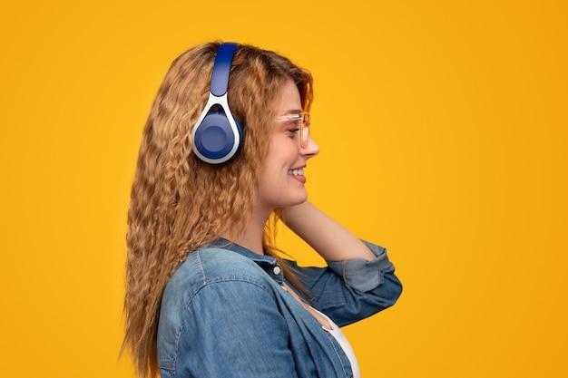 Nowoczesna kobieta uśmiechająca się i słuchająca muzyki