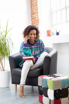 Nowoczesna kobieta używa swojego telefonu komórkowego w domu. miejsce na tekst.