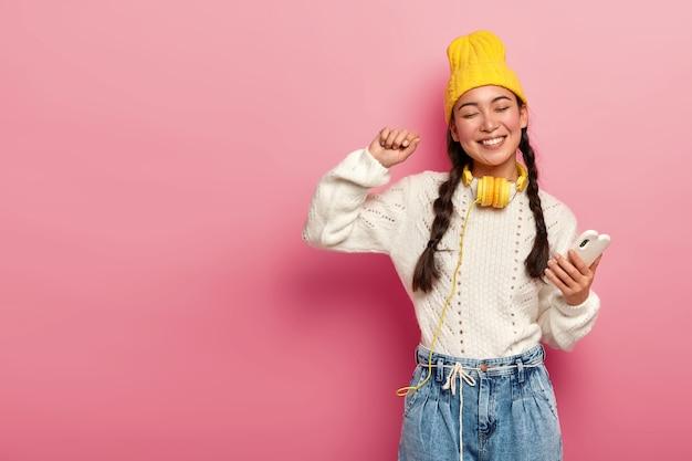 Nowoczesna kobieta w stylowych ubraniach cieszy się niesamowitym rytmem w słuchawkach, tańczy w rytm muzyki z podniesioną ręką na białym tle na różowym tle