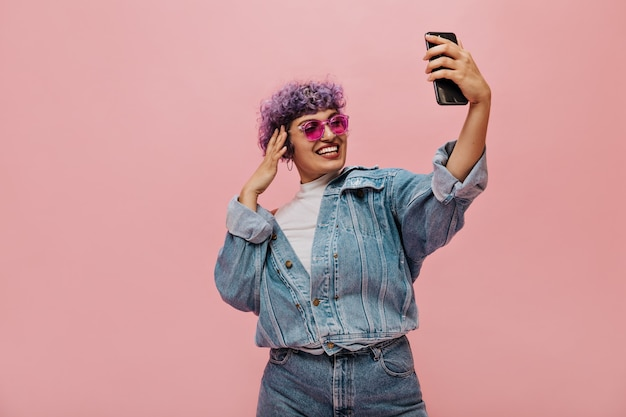Nowoczesna kobieta z fioletowymi włosami w fajnych okularach przeciwsłonecznych robi zdjęcie na różowo. uśmiechnięta pani w szerokich jasnych ubraniach bierze selfie.