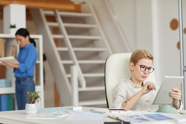 Nowoczesna kobieta za pomocą cyfrowego tabletu w miejscu pracy, kopia przestrzeń
